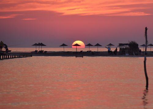 Západ slunce nad hotelovou pláží Resortu Divjaka 4* v Albánii.