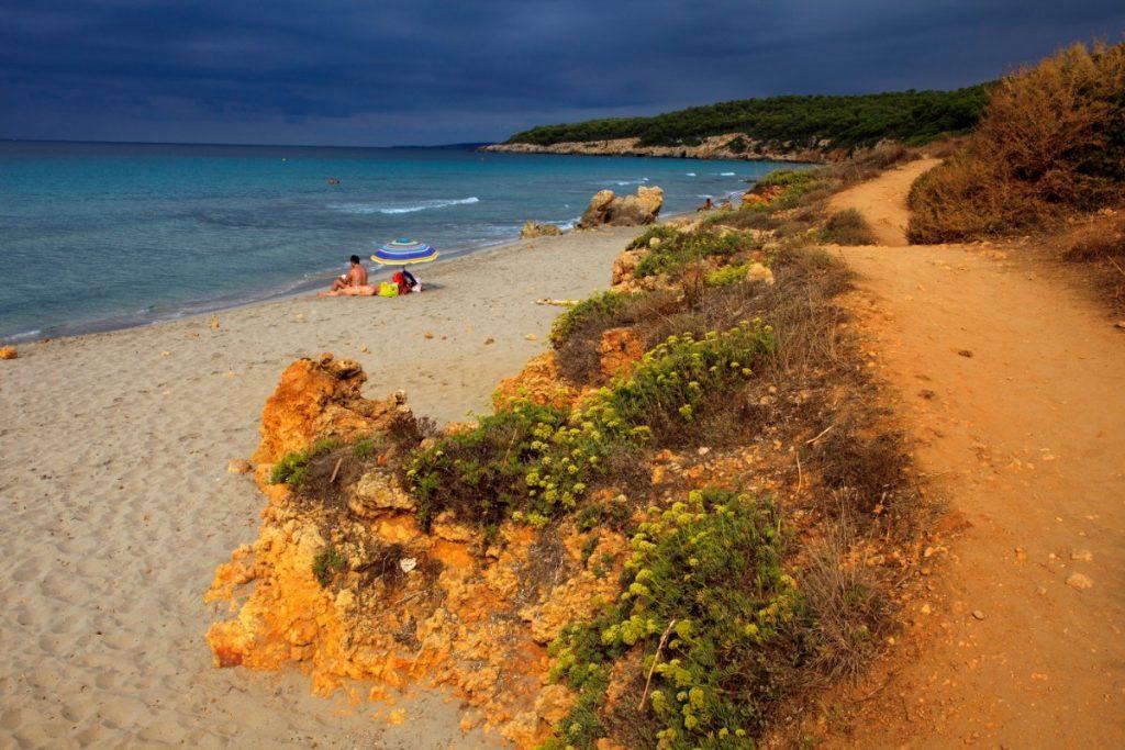 Turistická stezka podél nádherné pláže Santo Tomás na Menorce.