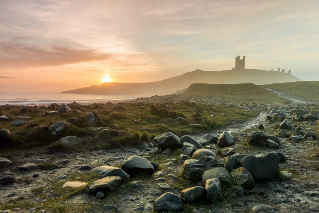 Hrad Dunstanburgh v ranním oparu.