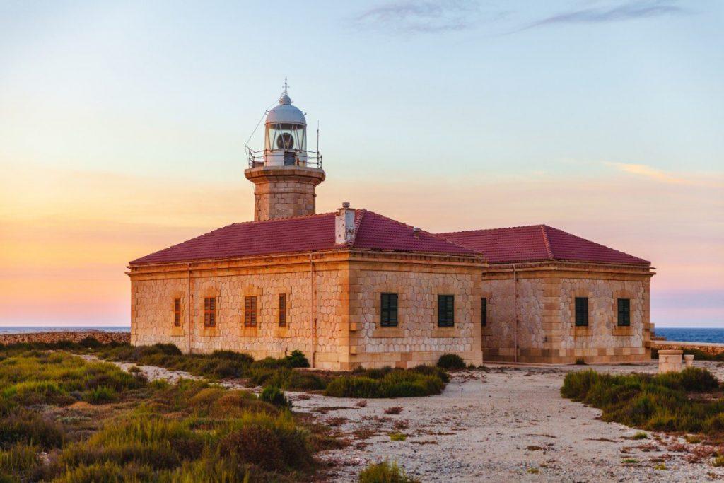 Romantický západ slunce u majáku Punta Nati na Menorce.