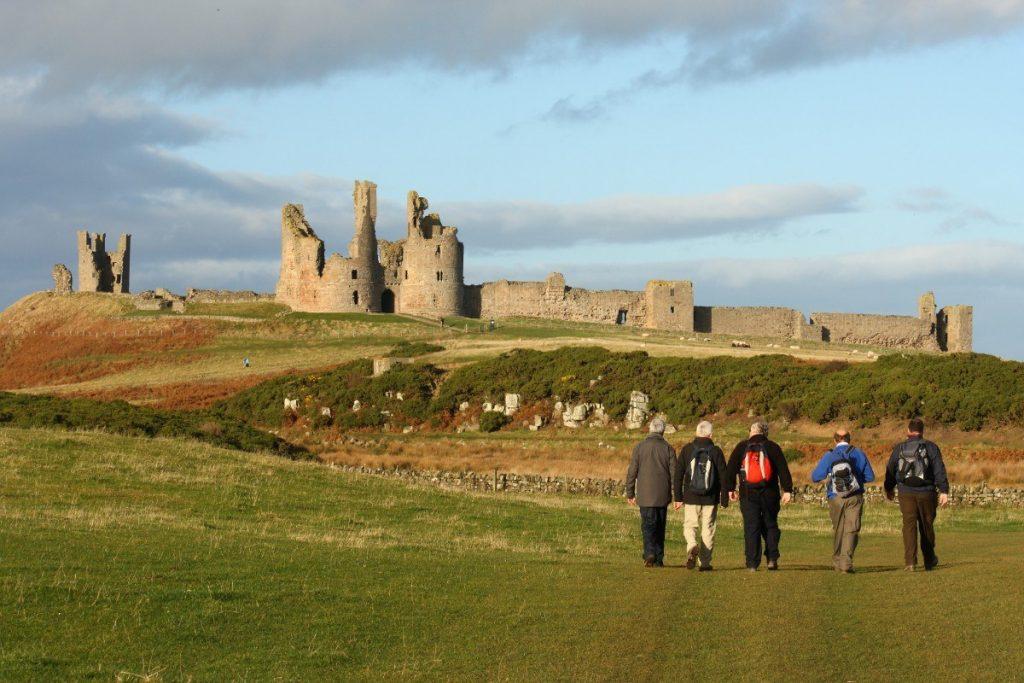 Turisté si užívají cestu ke středověkému hradu Dunstanburgh.