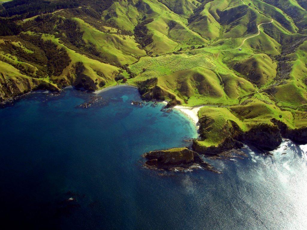 Letecký pohled na zelené kopce a hory při severním pobřeží Nového Zélandu.
