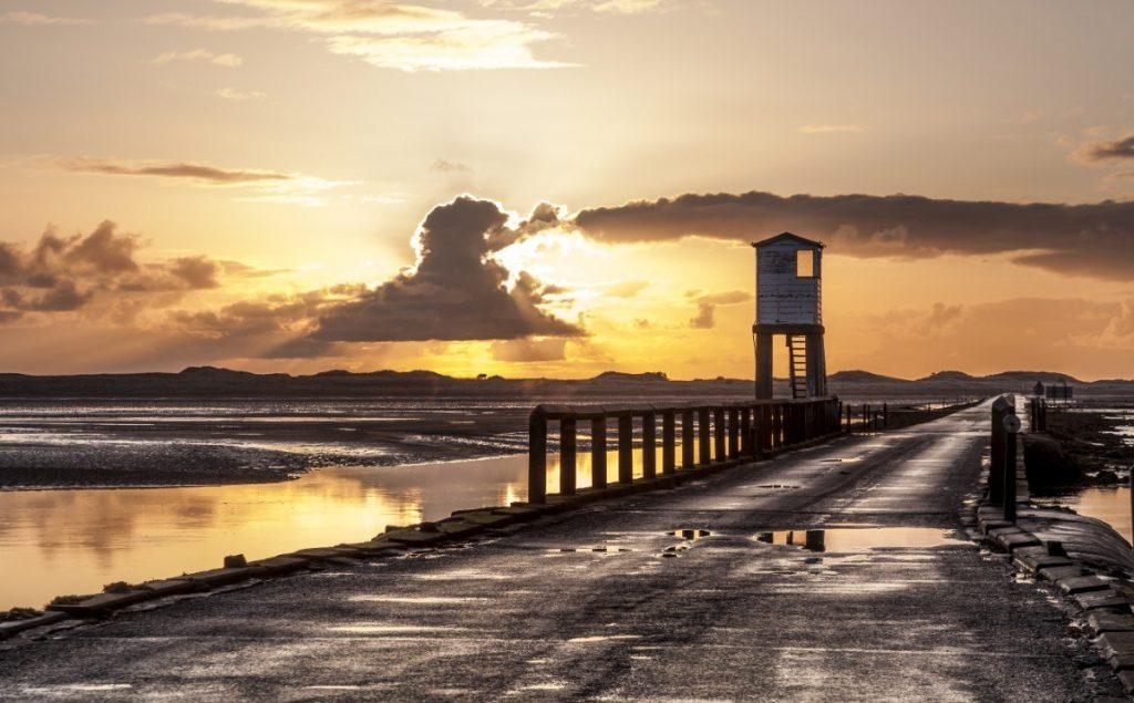 Východ slunce na pobřeží ostrůvku Holy Island.