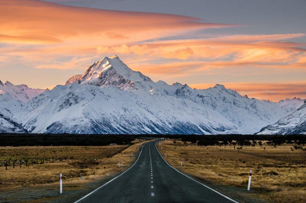 Pohled na majestátní horu Mount Cook a silnici vedoucí do stejnojmenné vesnice.