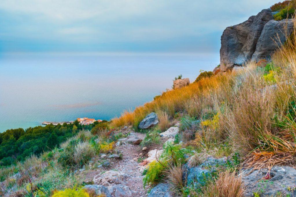 Horská pěšinka s výhledem na pobřeží v italské Kalábrii.