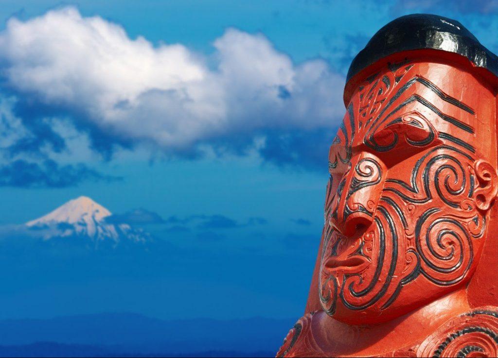 Tradiční maorská vyřezávaná socha s horou Mount Taranaki na pozadí.