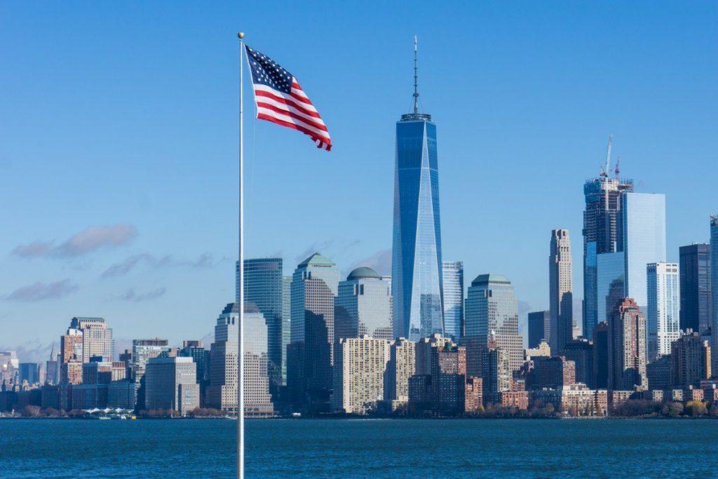 Americká vlajka, v pozadí řeka Hudson River a budova One World Trade Center.