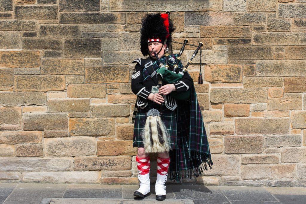 Pouliční muzikant v tradičním skotském oděvu.
