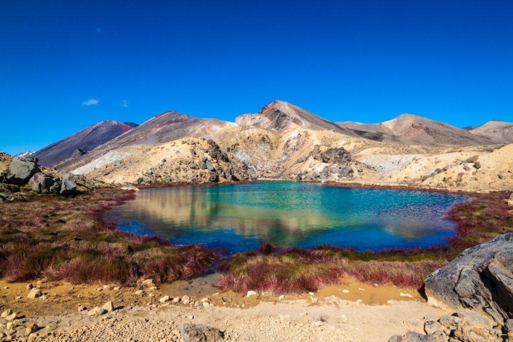 Smaragdové jezírko Emerald Lake v národním parku Tongariro je obklopeno sopečnou pouští.